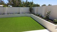 Artificial grass in a white concrete retaining wall