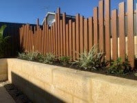 Reconstituted Limestone Retaining Wall with Wood Fences